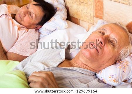 Close up of senior couple sleeping in bed. - stock photo