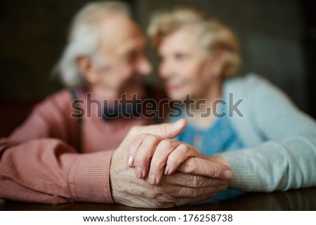 Close-up of senior female hand in that of her husband - stock photo