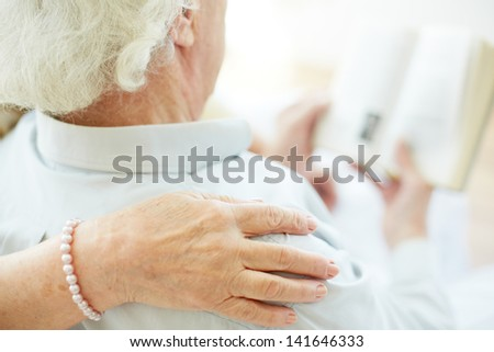 Close-up of senior female hand on her husband shoulder during reading