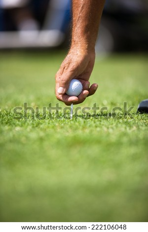 Close-up of Senior golfer preparing golf ball for teeing off.