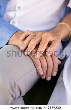 Close-up of senior man and woman holding hands