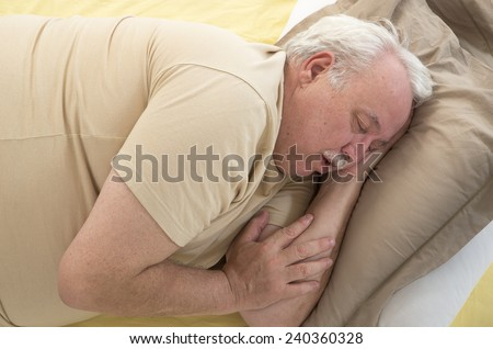 Close up of senior man sleeping and Snoring in bed - stock photo