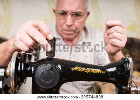 Close Up of Senior Man Threading Old Fashioned Manual Sewing Machine with Gray Thread - stock photo