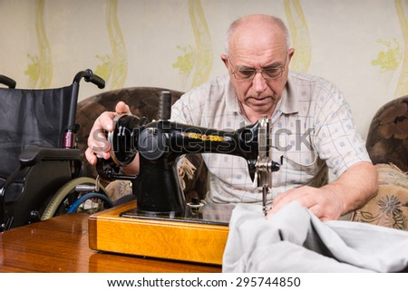 Close Up of Senior Man Using Manual Old Fashioned Sewing Machine to Mend Pants at Home - stock photo