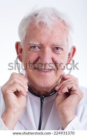 Close-up of senior physician with stethoscope in ears - stock photo