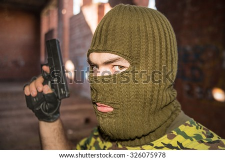 Close-up of serious armed criminal with black metal gun Russian policeman in camouflage mask with pistol. Green mask on head Inside building Look at camera  - stock photo