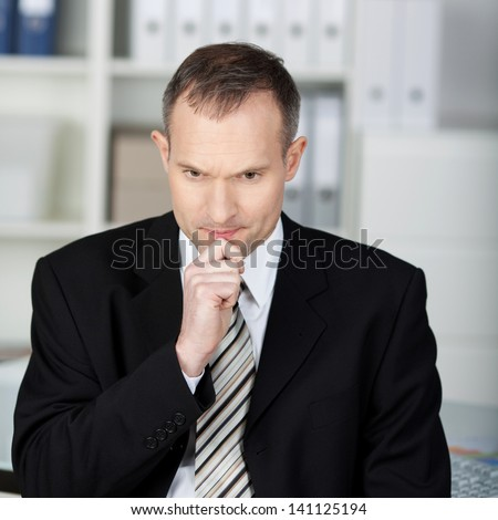 Close up of serious businessman thinking at something at the office - stock photo