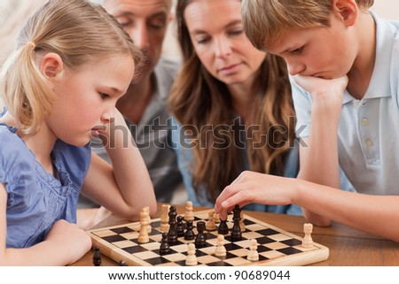 Close up of serious children playing chess in front of their parents in a living room - stock photo