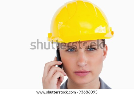 Close up of serious female architect on her cellphone against a white background