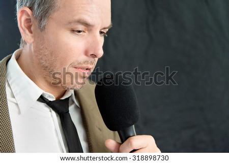 Close-up of serious man speaking into microphone, side. - stock photo