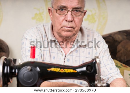 Close Up of Serious Senior Man Wearing Eyeglasses Using Old Fashioned Sewing Machine at Home in Living Room - stock photo