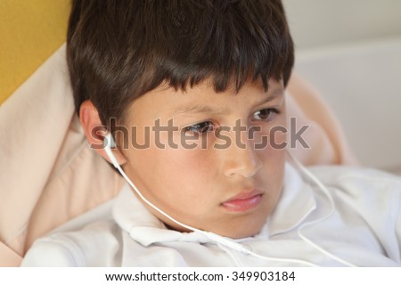 Close-up of serious young boy playing computer game wearing ear buds - with shallow depth of field - stock photo