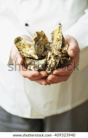 Close Up of Server with  Fresh Shucked Oysters  - stock photo