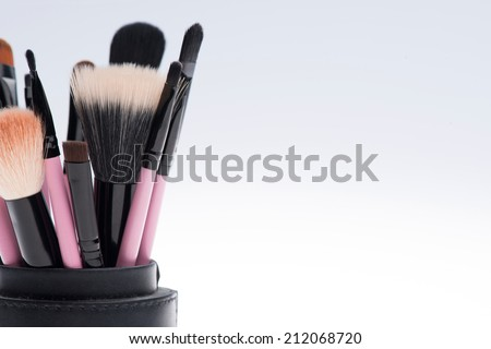 Close-up of Set of professional  different sizes make-up brushes in black tube isolated on white background with copy place  - stock photo