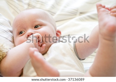 Close up of seven month old baby lying on back - stock photo