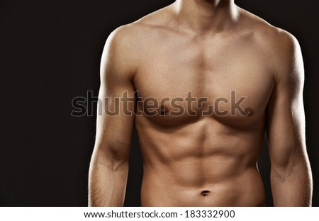 Close up of sexy male's torso, isolated on black - stock photo