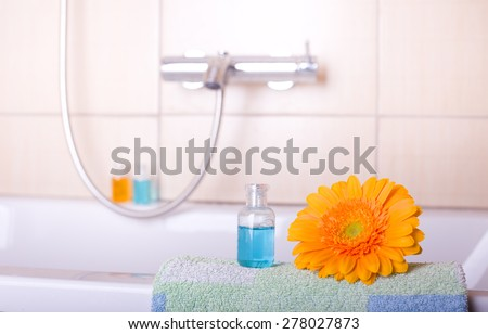 Close up of shampoo bottle with flower on bathtub