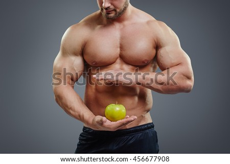 Close up of shirtless bodybuilder holding an apple in his hands. Fit man holding apple on six pack abs background. Healthy diet concept. - stock photo