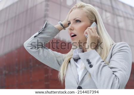 Close-up of shocked businesswoman communicating on cell phone against office building - stock photo