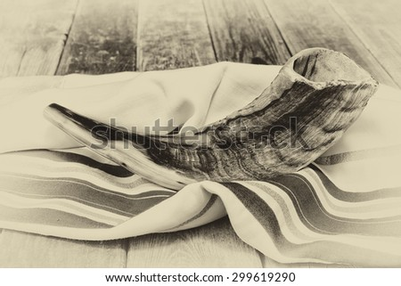 close up of shofar (horn) on white prayer talit. room for text. rosh hashanah (jewish holiday) concept . traditional holiday symbol. black and white old style photo  - stock photo