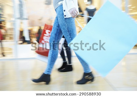 Close Up Of Shoppers Feet Carrying Bags In Shopping Mall - stock photo