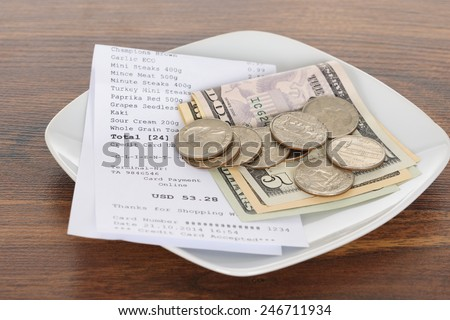 Close-up Of Shopping Receipt With American Dollars On Wooden Table - stock photo