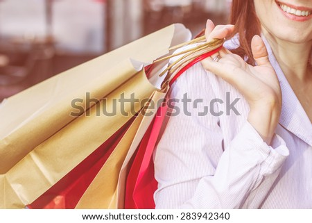 Close up of Shopping Woman holding colorful bags. Caucasian unrecognizable female on street. - stock photo