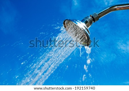 Close-up of shower head with flowing water against blue sky.