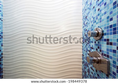 Close up of shower unit of modern bathroom with wave pattern and  turquoise, blue mosaic tiles. - stock photo