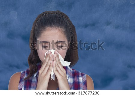 Close-up of sick woman sneezing in a tissue against cloudy sky