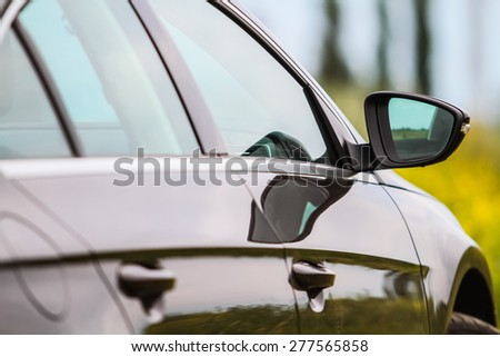 Close up of side rear-view mirror on a modern car  - stock photo