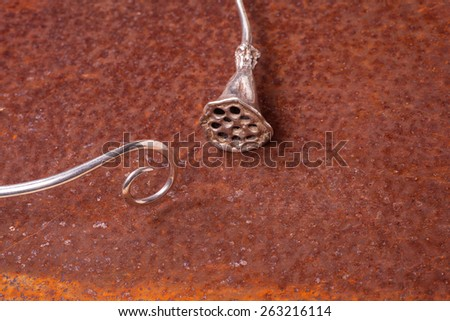 Close up of silver necklace on rusty iron, manufactured by Ornella Salamone - stock photo