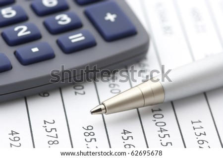 Close-up of silver pen and calculator on paper table numbers. - stock photo
