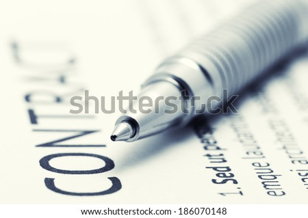 Close-up of silver pen on contract. Selective focus on top of pen. Toned image. - stock photo