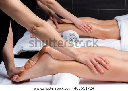 Close up of simultaneous leg massage on couple in spa.Two physiotherapists applying pressure on couples legs.  - stock photo