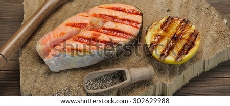 Close-up Of Single BBQ Grilled Salmon Steak On The Wood Board - stock photo