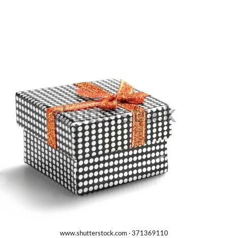 Close Up Of Single Gift Box With Dotted Black White Pattern, Orange Ribbon And Bow, Isolated On White Background,  Horizontal Image With Copy Space, Front View - stock photo