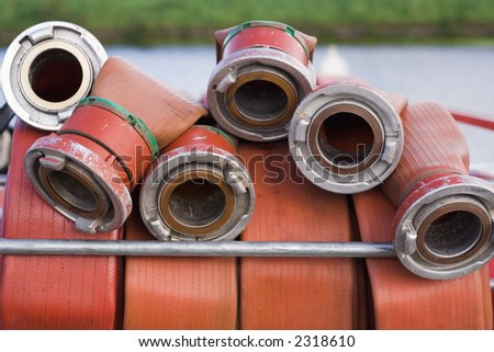 Close-up of six aluminum end of rolled up firehoses on a vehicle. - stock photo