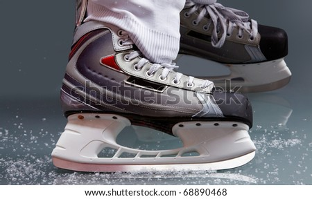 Close-up of skates on player feet during ice hockey - stock photo