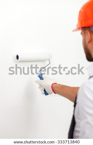 Close up of skillful young builder painting walls of building inside. He is standing and looking forward with joy. The man is holding a roller - stock photo