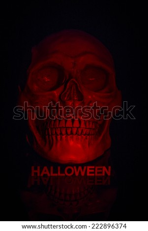 Close up of skull with letters below spelling out the word halloween and lit by a red light to give a spooky red glowing skull on a black background - stock photo