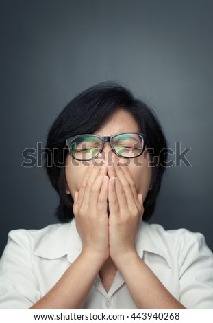 Close up of sleepy young asian girl yawning. Tired and sleepy of glasses woman. Short hair female sneezing. Illness, depression and allergy concept.  - stock photo