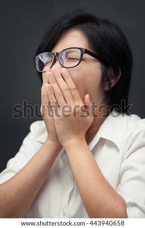 Close up of sleepy young asian woman yawning. Tired and sleepy of glasses girl. Sleepy of business woman on grey wall. Short hair female sneezing. Illness, depression and allergy concept.  - stock photo