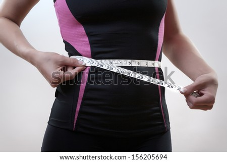 Close-up of slender woman measuring her waist - stock photo