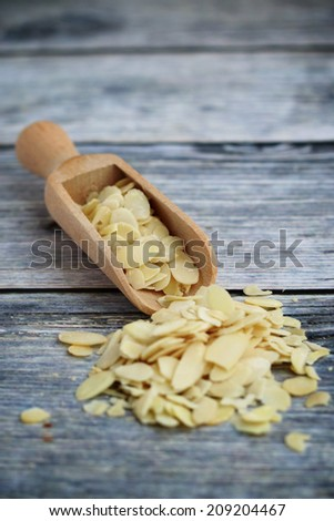 Close up of sliced almond nuts on wooden spoon