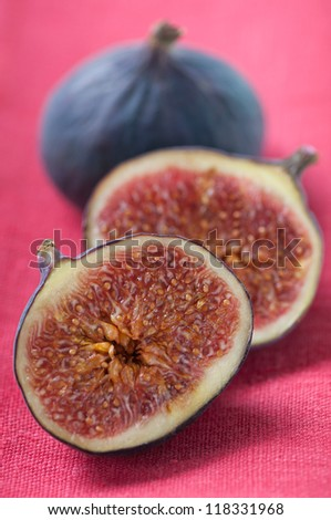 Close-up of sliced and whole fig fruits on a red serviette, studio shot