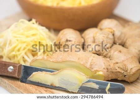 Close up of sliced fresh ginger roots with knife on chopping board for food preparation background  - stock photo