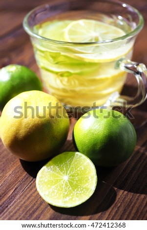 Close up of sliced of lime and lime juice on wooden table.
