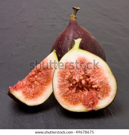 Close up of Sliced ripe figs isolated against dark slate background. - stock photo