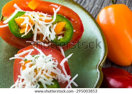 Close up of slices of tomatoes with pepper and cheese topping.